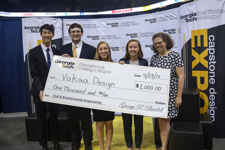 Vakaa Design — a team comprising, left to right, Justin Liu, Chris Folsom, Kailee Unangst and Hannah Davis — accepts the first-place check for civil and environmental engineering at the spring 2019 Capstone Design Expo alongside Associate Professor Kari Watkins. The team had to design the alignment of new express lanes along Interstate 285 in northwest Atlanta, including the structural elements to supported the elevated lanes. (Photo: Amelia Neumeister)