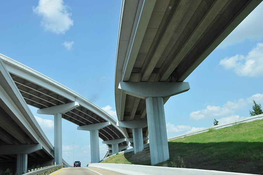 Looking up at several levels of highway bridges and overpasses stretching across roads with blue sky above. (Photo Courtesy: Drriss & Marrionn via Flickr)