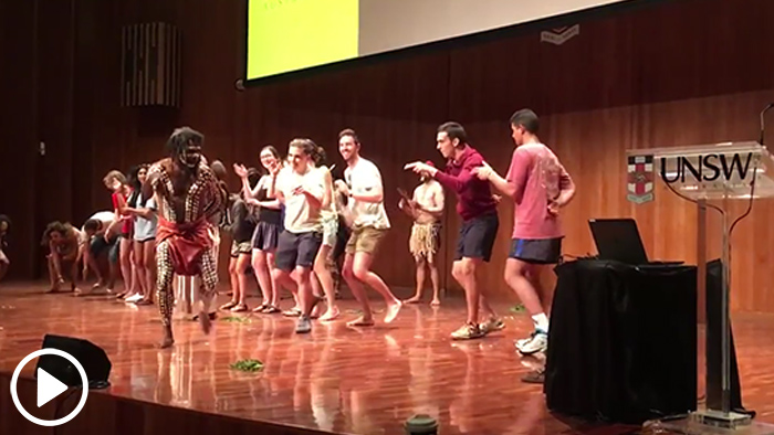 Video still frame showing Andrew Melissas and several other students participating in a traditional dance honoring an Australian Aboriginal culture during his study abroad trip to the country.