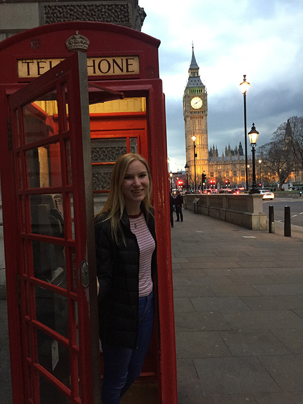 Claire Anderson in an old telephone booth in London that still works for emergency numbers. Big Ben and Westminster Abbey are in the distance.
