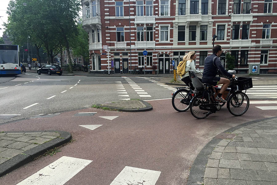 "Bicyclists ride through a protected intersection for bikes and pedestrians in the Netherlands. ""The intersection has no signals, but light rails, cars, buses, bikes and pedestrians all move through it without conflict,"" according to Anna Nord. (Photo: Anna Nord)"