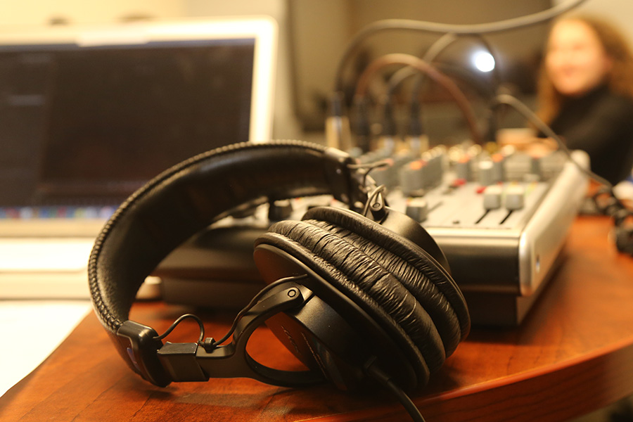 Headphones in front of an audio mixer and laptop during a podcast recording. (Photo: Jess Hunt-Ralston)