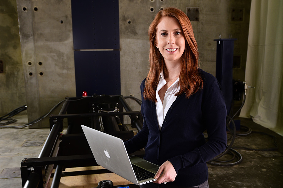 Lauren Stewart stands with a laptop in the Structural Engineering and Materials Lab. (Photo: Gary Meek)