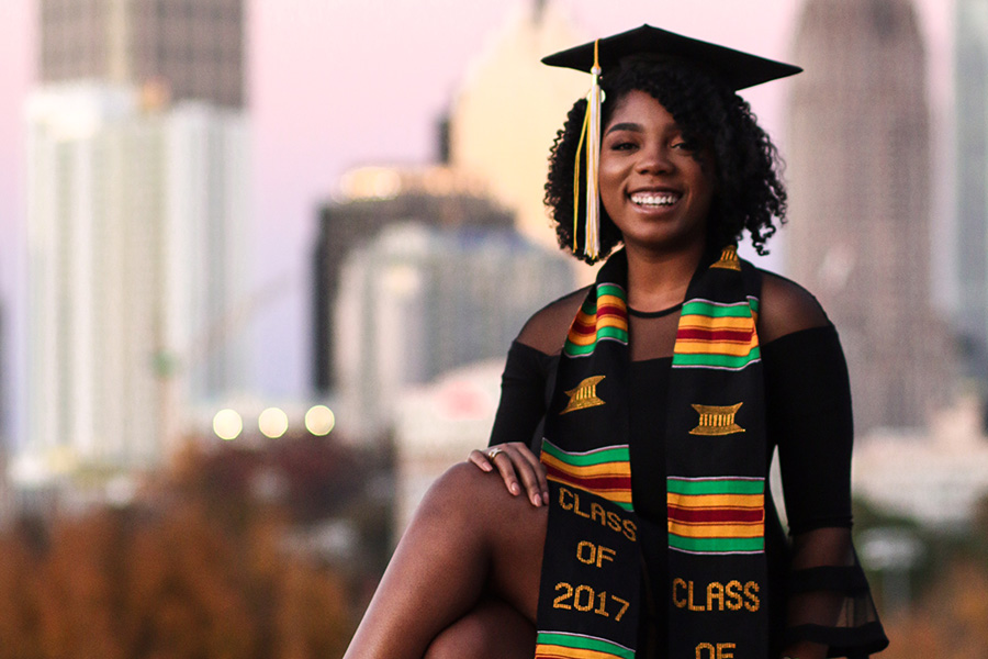 Sharani White poses in her cap and gown with Midtown Atlanta in the background. White struggled in her first year, to the point that she almost had to transfer. But now she's finished her civil engineering degree and has been accepted to graduate school. (Photo: Titilayo Funso)