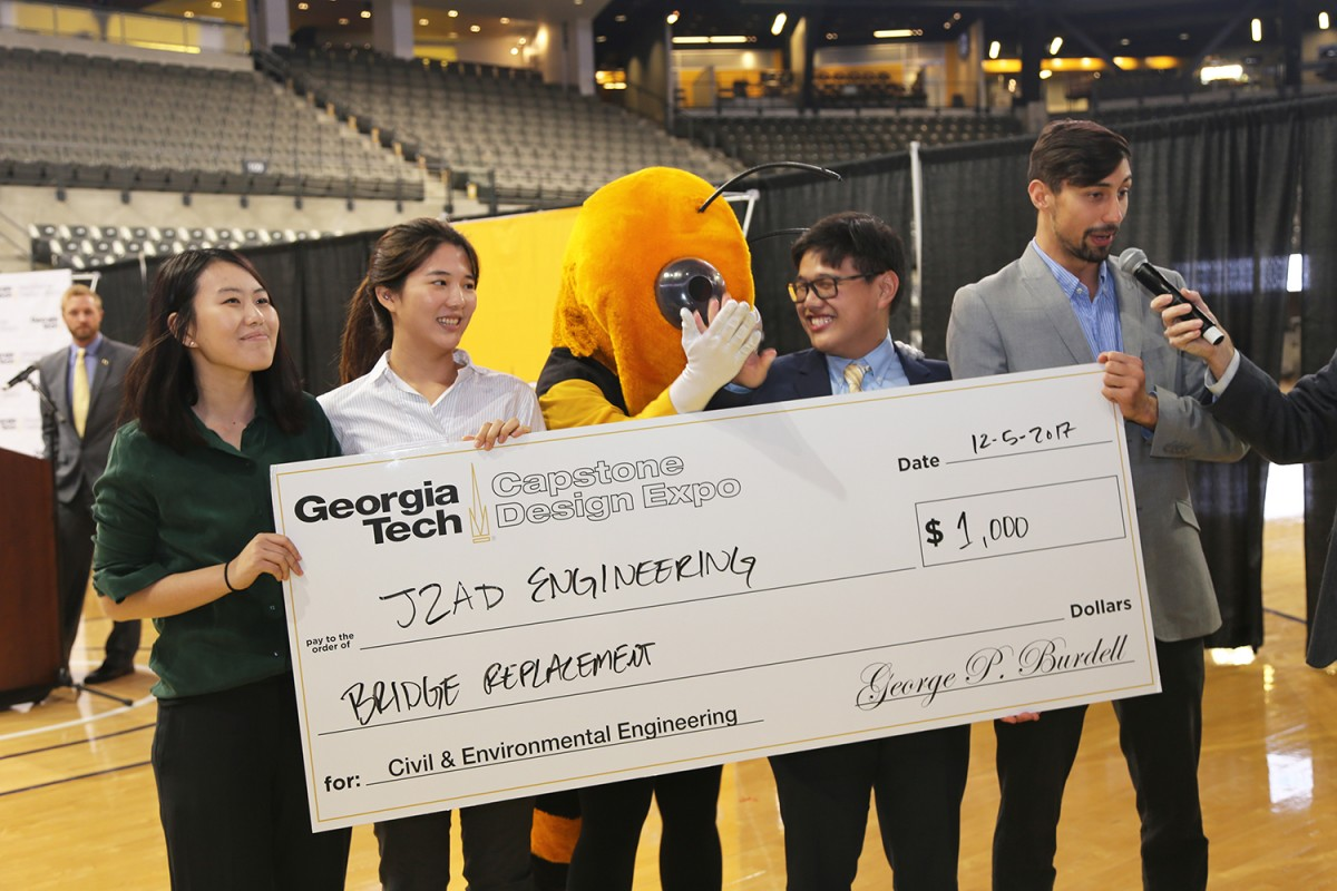 Team J2AD Engineering won the civil and environmental engineering award at the fall 2017 Capstone Design Expo. From left, Jessie Lei, Jiyoon Oh, Austin Foo and Donald Smith accept their winnings from Buzz (yellow jacket, center). (Photo: Jess Hunt-Ralston)