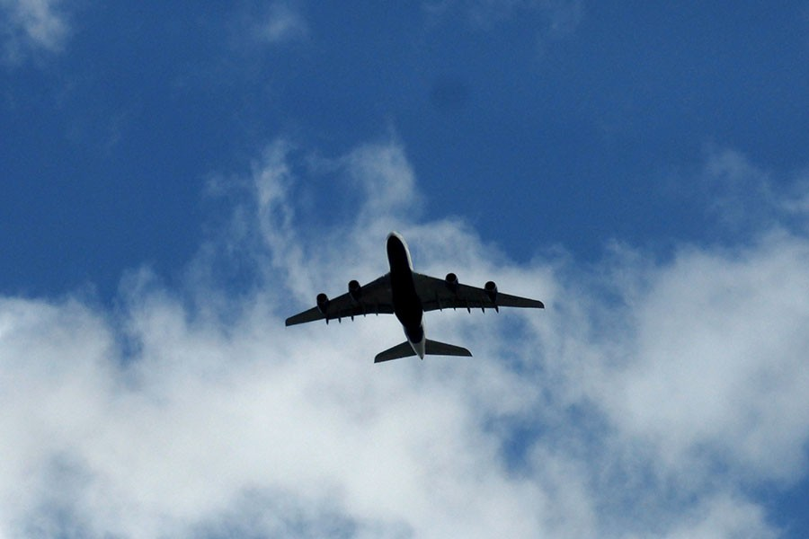 a commercial airplane viewed from below is flying against a blue sky with white clouds