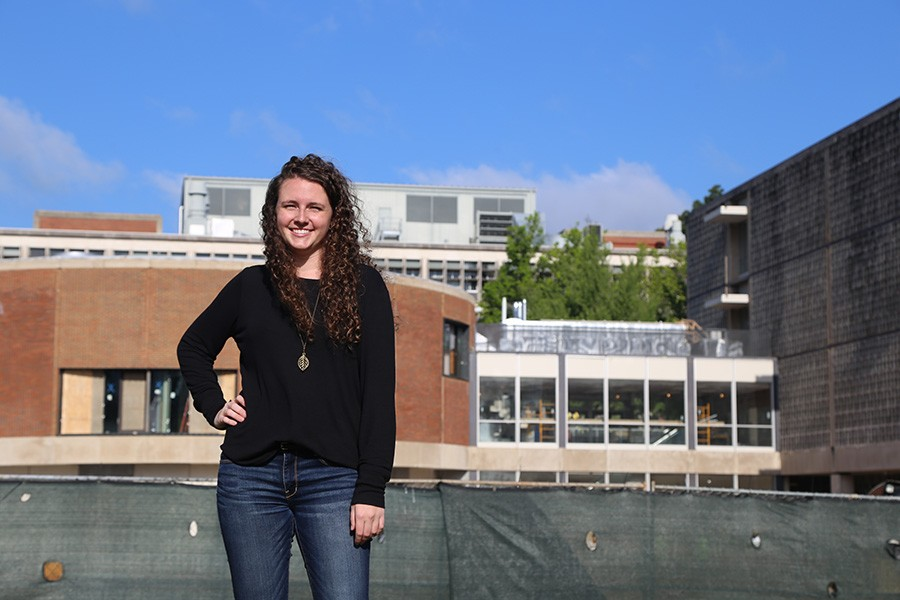 Rachel Brashear, a fourth-year civil engineering undergraduate, stands in front of the Van Leer Building and the under-construction Interdisciplinary Design Commons. Brashear has been working as the project's on-site engineer with Gilbane Building Company. (Photo: Jess Hunt-Ralston)