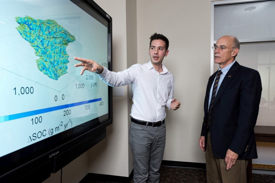 Yannis Dialynas, a hydrology Ph.D. student in Georgia Tech's School of Civil and Environmental Engineering, and Georgia Tech Provost Rafael L. Bras, discuss a model of soil erosion. This research is studying the role of erosion on carbon cycling. (Photo: Rob Felt)