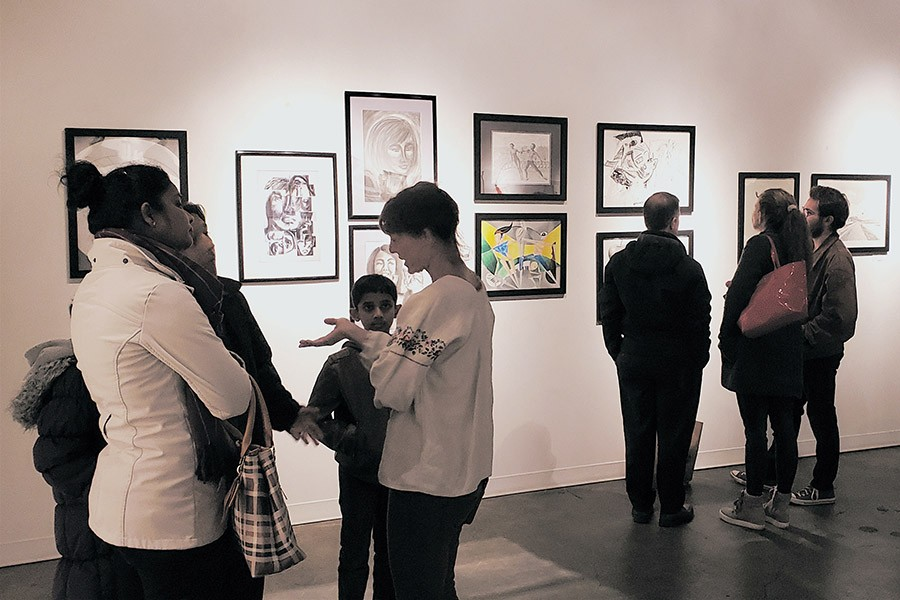 Visitors consider the artwork created by students in Francesco Fedele's Visual Arts and Geometry course at the Kai Lin Gallery Dec. 11. The drawings hung for one night at the gallery to celebrate the students' work in the class, which connected advanced geometry with art through the lenses of Einstein and Picasso.