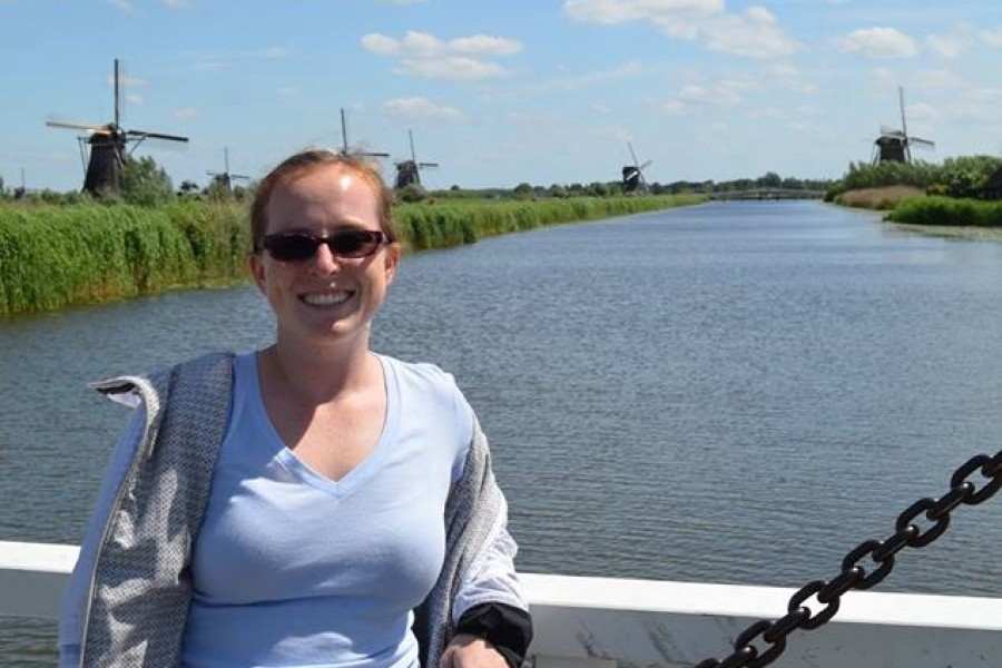 Ph.D. student April Gadsby stands on a bridge over a canal in the Netherlands in 2017 with a few of the country's famed windmills in the background. (Photo Courtesy: April Gadsby)