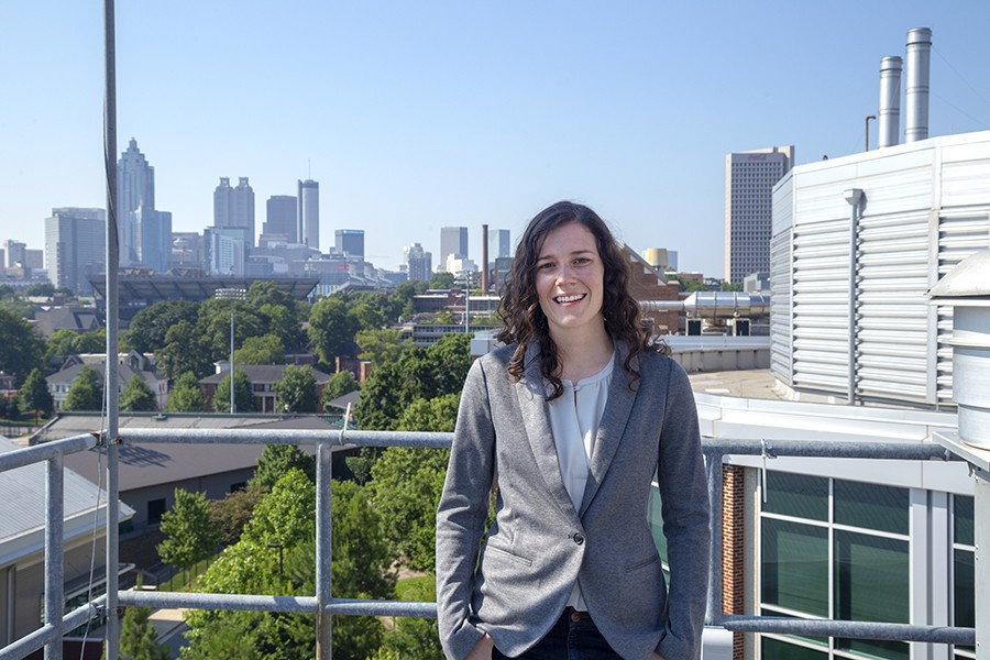 Assistant Professor Jennifer Kaiser, wearing a gray blazer, poses on campus with the Atlanta skyline in the background.