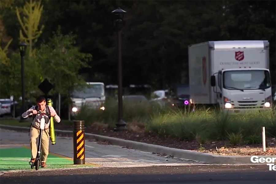 Screenshot of North Avenue Smart Corridor: One Year Later video, with student riding a scooter on separated bike path and traffic in vehicle lanes.