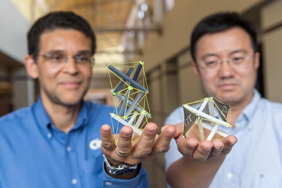 "Georgia Tech researchers Glaucio Paulino, left, and Jerry Qi hold 3-D printed objects that use tensegrity, a structural system of floating rods in compression and cables in continuous tension. They've developed a new way to create structures with ""memory"" that can expand dramatically when heated. (Photo: Rob Felt)"