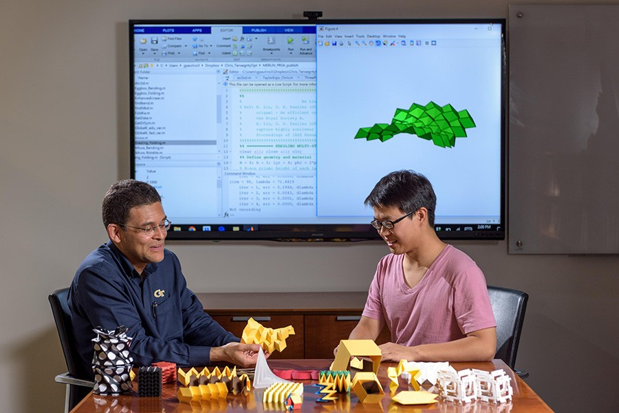 Researchers Glaucio Paulino (left) and Ke Liu with origami structures that can be simulated in new software. (Photo: Rob Felt)