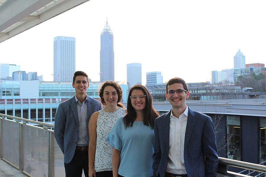 The four members of the student team River Recon pose in front of the Atlanta skyline