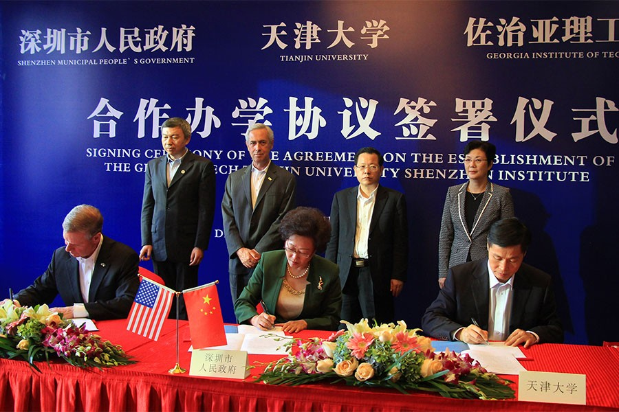 "Georgia Tech President G.P. ""Bud"" Peterson, seated left, signed an agreement in a ceremony in Shenzhen, China, Dec. 2 to create a new collaboration with the City of Shenzhen and Tianjin University. Co-signers with Peterson are Vice Mayor Yihuan Wu of Shenzhen Municipal People's Government, center, and Tianjin University President Denghua Zhong, right."