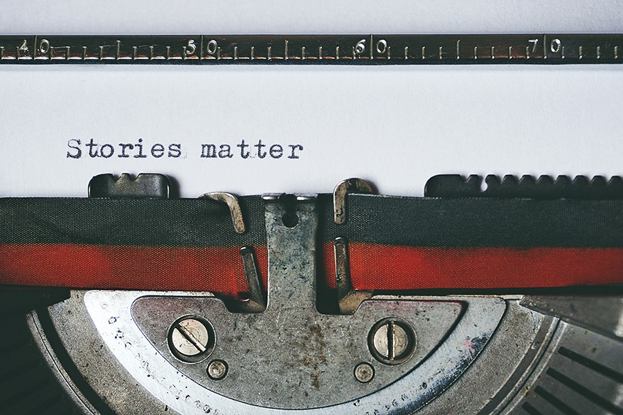 """A close up view of a typewriter ribbon with with the words """"Stories Matter"""" typed on a piece of white paper"""