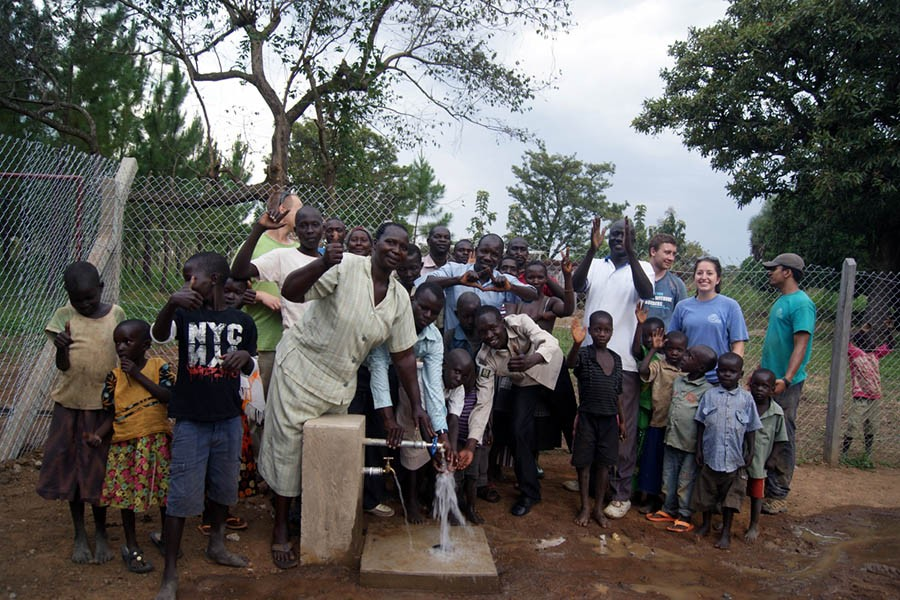 Oloo, Uganda, community members stand with the water pump that Engineers Without Borders has helped them construct.