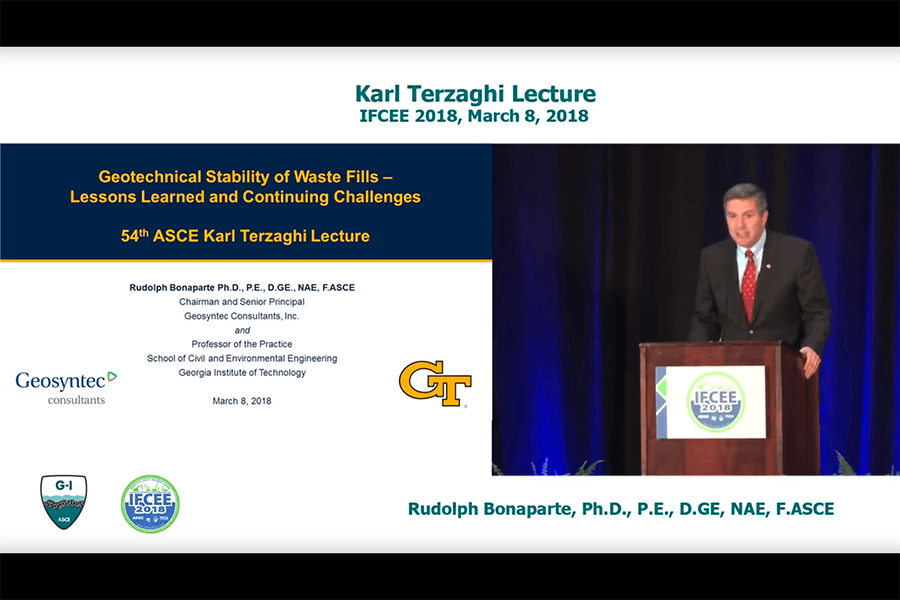 "Video screenshot of Rudy Bonaparte delivering the Karl Terzaghi Lecture on March 8, 2018. Split screen shows Bonaparte at a podium on the right and his title slide on the left, ""Geotechnical Stability of Waste Fills – Lessons Learned and Continuing Challenges."""