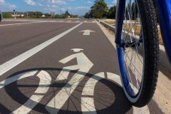 A bicyclist rides in a marked bike lane alongside a multi-lane road in Lutz, Florida. A new study of bicycle infrastructure from a team of School of Civil and Environmental Engineering researchers has found we don't know much yet about how well bicycle infrastructure like these lanes protect riders. (Photo Courtesy: Daniel Oines via Flickr.)