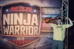 Civil engineering undergrad Elie Cohen flexes his biceps while holding his mandolin in front of an American Ninja Warrior 2018 sign. (Photo Courtesy: NBC)