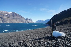 University of Oregon volcanologist Thomas Giachetti stands with an iceberg washed ashore by a landslide-generated tsunami in Greenland in June. (Photo: Hermann Fritz)