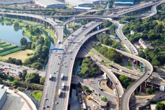 Cars and trucks drive on an interchange with roads branching off in several directions.