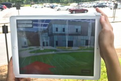 Using an iPad and an augmented reality model like this, students and other future users of Georgia Tech's Living Building will be able to tour the facility long before it opens, offering input on some of the design decisions. A user shows how the model will work at the future site of the building. (Photo Courtesy: Kendeda Fund Living Building Chronicle)