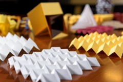Paper origami models demonstrate various folding patterns that can be useful in engineering applications. In the foreground is a sheet in the Miura-ori pattern. (Photo: Rob Felt)