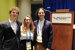 Three Georgia Tech students stand by the podium at the Water Environment Federation's student design competition