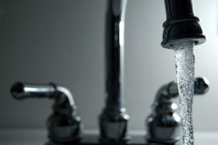 Water pouring from a faucet. (Photo Courtesy: Steve Johnson via Flickr)