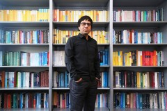 Professor Arash Yavari stands in front of his packed bookcase in his Mason Building office. Yavari has embarked upon a four-year research project to lay the mathematical foundations for cloaking structures from earthquakes and other stress waves. (Photo: Jess Hunt-Ralston)
