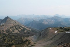 A photo of large mountains with a few trees and small white spots of snow in Yellowstone National Park.