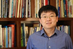 Ph.D. student Tuo Zhao stands in front of shelves filled with books. (Photo Courtesy: Center for Teaching and Learning)