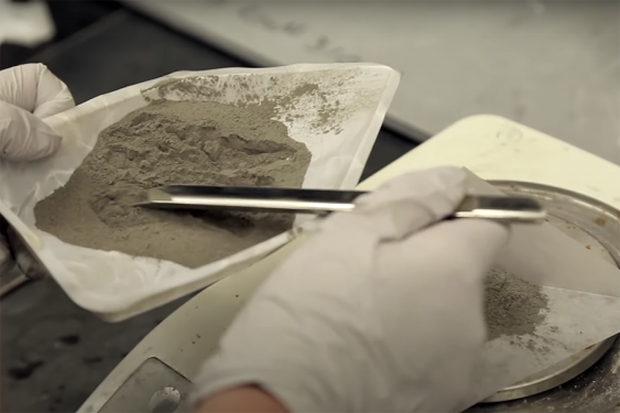 A close up of coal ash and a silver instrument in a dish held by hands in white latex gloves