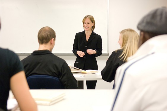 Standing before a white board wearing a black blazer, Lisa Rosenstein leads a class.