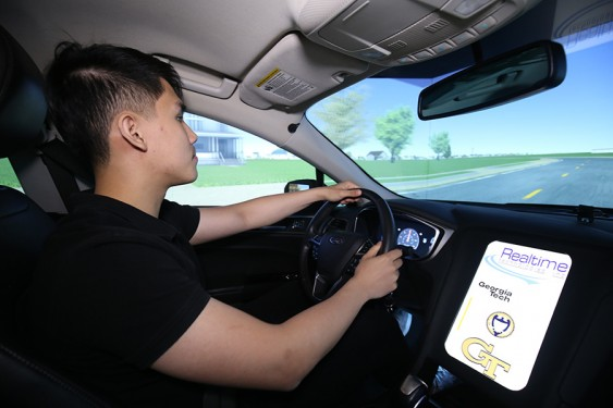 Ph.D. student Anye Zhou drives the new full-size simulator in Srinivas Peeta's lab. The simulator is built from a 2013 Ford Focus and includes wraparound screens to immerse test drivers in the simulated environment. (Photo: Candler Hobbs)