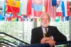 Georgia Tech President Emeritus G. Wayne Clough stands with his arms resting on a stair handrail with international flags hanging in the background.